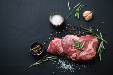 Above view of raw ribeye steak with spices over black background