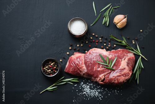 Fotografiet Above view of raw ribeye steak with spices over black background