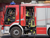 Italian firefighters climb on firetrucks during an emergency