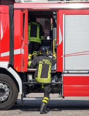 Italian firefighters climb on the trucks of firefighters