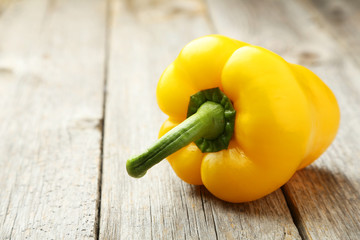 Yellow pepper on grey wooden background
