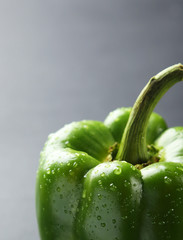 Green pepper with water drops on grey background