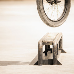 close-up of bicycle wheels doing trick by rail
