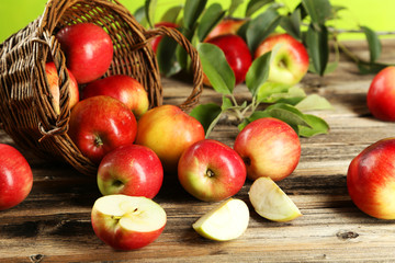 Apples in basket on brown wooden background