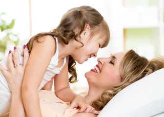 Happy mom playing with her kid in bed enjoying  sunny morning in
