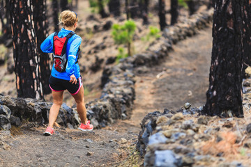Young woman trail running in forest