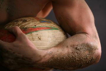 Braccio sporco di fango con pallone da rugby