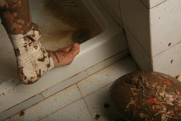 Piede fasciato, pallone da rugby e doccia sporchi di fango