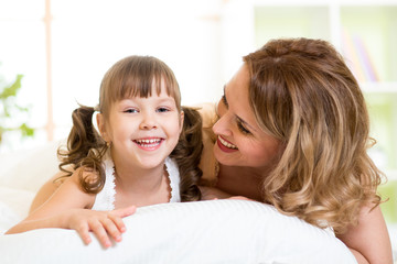 Portrait of a joyful mother and her daughter child lying on bed