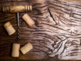 Corkscrew and corks on an old wooden table.