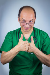 Portrait of doctor in green uniform showing ok sign