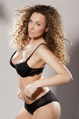Studio portrait of a seductive girl with curly hair