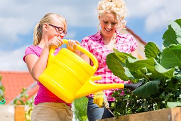 Familie bei Gartenarbeit vor ihren Haus