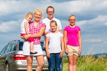 Familie stehet zusammen vor Auto