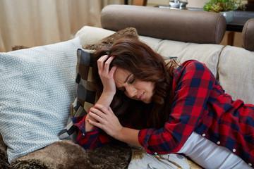 junge frau mit kopfschmerzen auf der couch