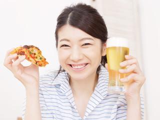 ピザとビールを持つ女性