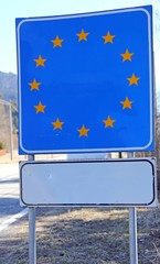 blue sign with yellow stars in the border area of a European bor