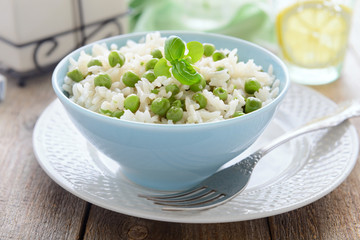 Risotto with green peas in blue bowl