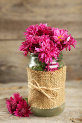Beautiful purple chrysanthemums in glass on wooden background