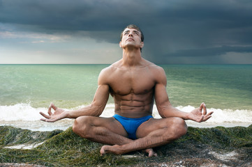 Athletic man doing yoga on sea shore