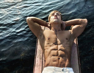 Muscular young man lying on wooden jetty against sea water backg