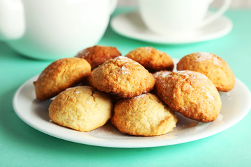 Coconut cookies on plate on green background