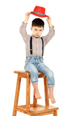 Portrait of a funny little boy sitting on a high stool in a red