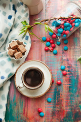 Cup of espresso with colorful sweets on wooden table