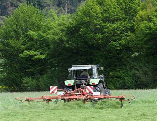 Traktor beim Heuwenden