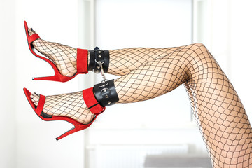 Sexy legs with ankle-cuffs in black fishnet stockings