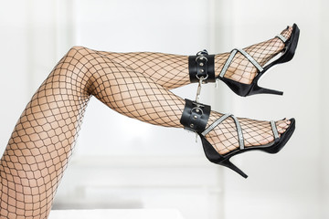 Cuffed legs of a woman wearing stockings and elegant high heels