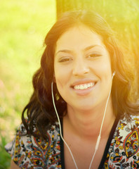 Beautiful smiling woman listening to music outdoors