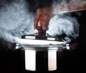 hand of chef open hot stream pot with beautiful studio lighting