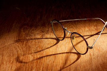 Spectacles with long shadow on wooden surface