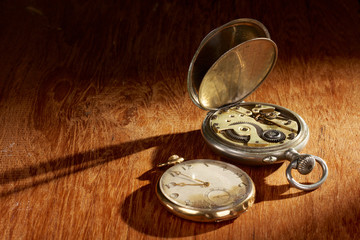 Pocket watches with long shadows on a wooden table