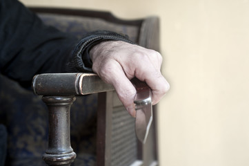 Hand close up of a man sitting on chair holding knife