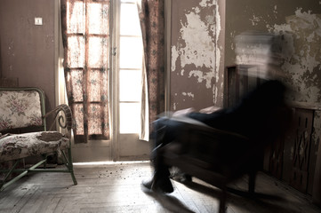 Man on rocking chair in a dirty old room