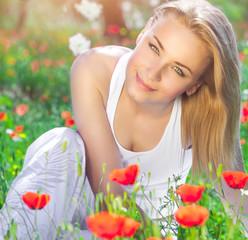 Beautiful girl on poppy flower field