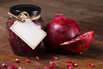 Pomegranate on a wooden table with a jar