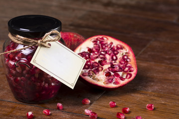 Pomegranate on a wooden table with a jam