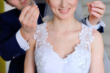 Groom wears a pendant around bride's neck