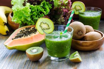 Green tropical smoothie with kiwi, papaya and salad leaves