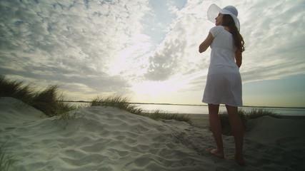 Young woman in summer dress walks along sand dunes