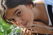 Leinwanddruck Bild - Mädchen trinkt am Brunnen