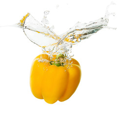 yellow pepper falling in water on the white background