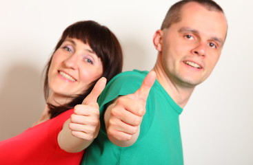 Smiling woman and man showing thumbs up