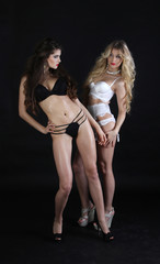 Blonde and brunette standing next to each other