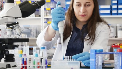 technician in the laboratory with a pipette and test tube