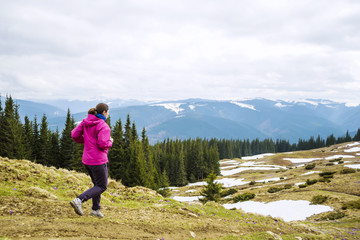 young caucasian female running in montains