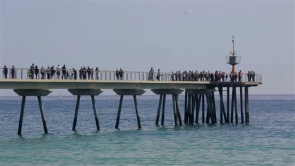 Footbridge over the sea with people walking.
